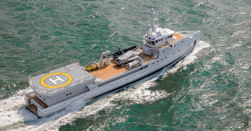 Game Changer yacht on sea viewed from above with helipad and toys on upper deck visible