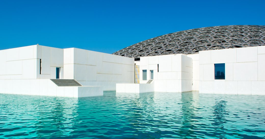water feature which surrounds the Louvre Abu Dhabi with perforated silver dome in shot