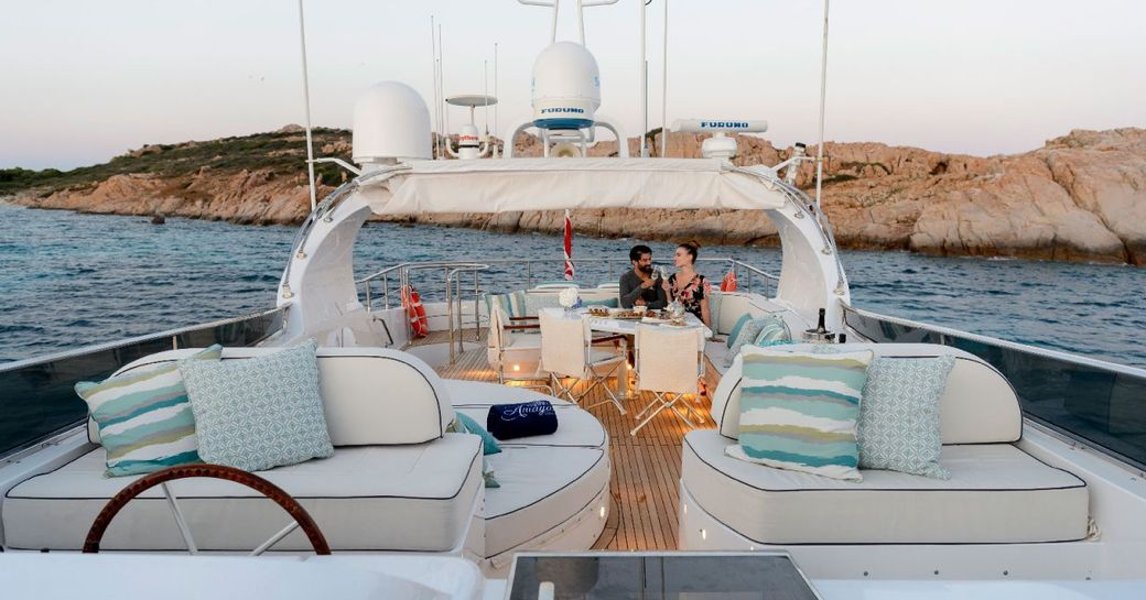 Charter guests sit on the flydeck of superyacht AMAYA