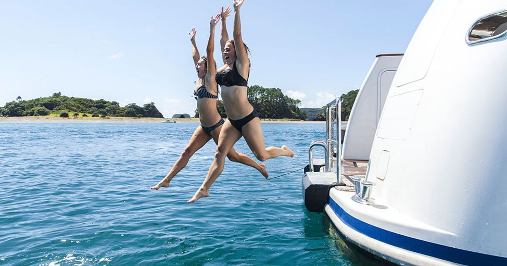 charter guests aboard expedition yacht RELENTLESS jump into the ocean from the swim platform