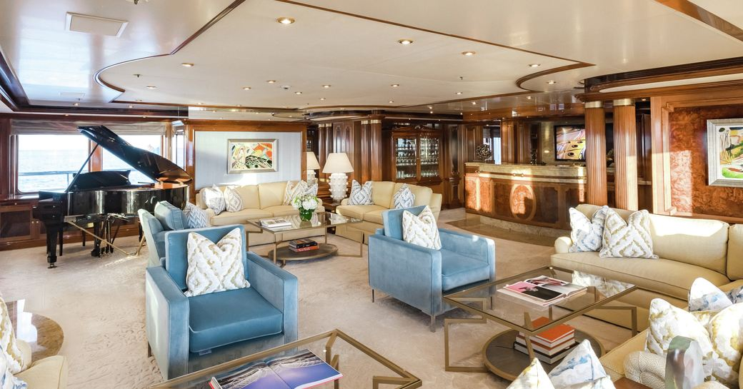 main salon with sofas and armchairs and piano on board superyacht TITANIA