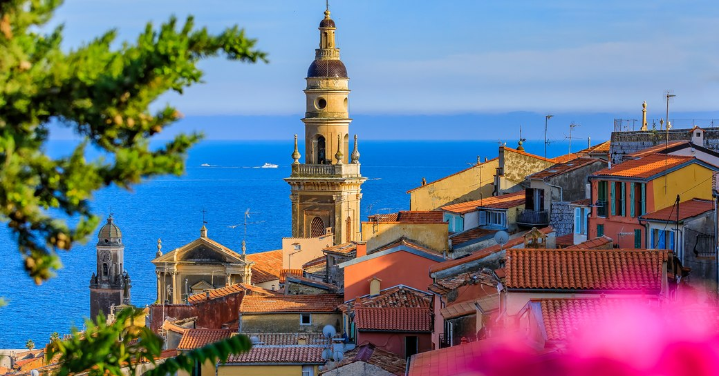 Old town of Menton, French Riviera. Clock tower rising over rooves with sea in background.