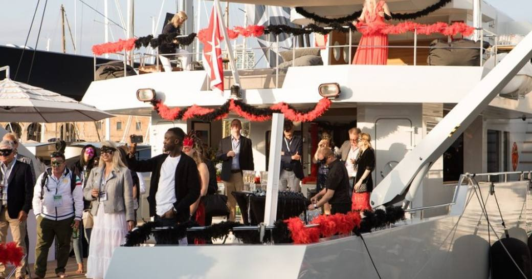 Crew and visitors engaging in a themed mask party onboard motoryacht, with further visitors celebrating dockside adjacent to yacht.