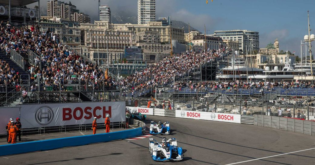 Two racers speeding round track at Monaco E-Prix, surrounded by stands of spectators.