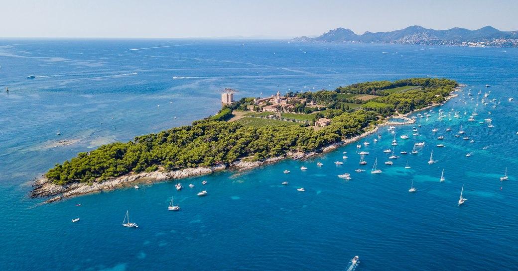 Aerial drone shot view of yachts between Ile Sainte Marguerite and Ile Saint Honorat in mediterranean sea