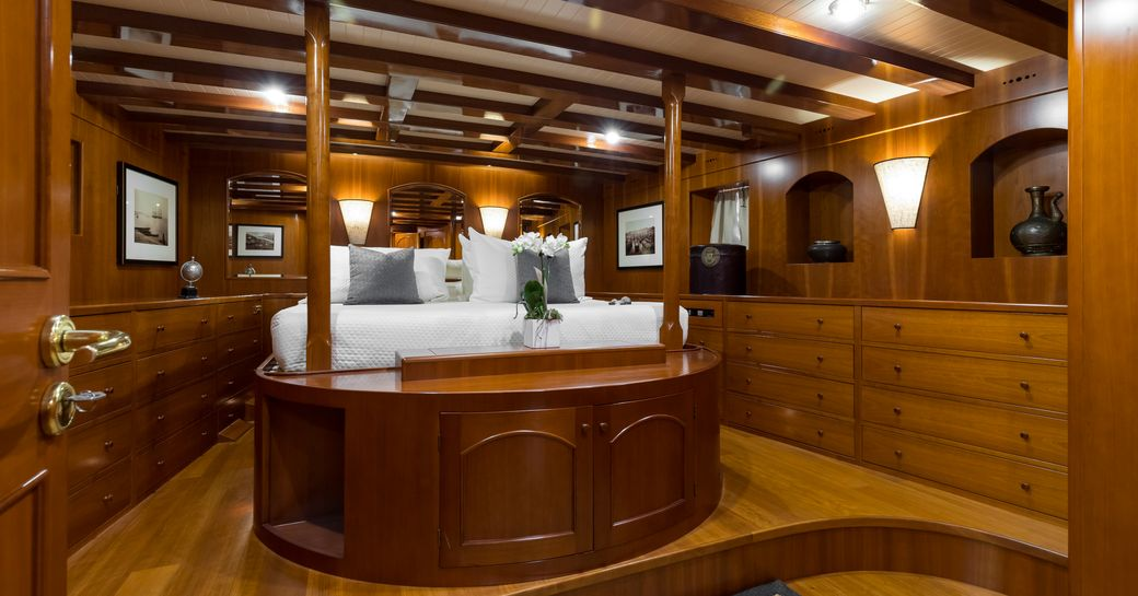 master stateroom on luxury charter yacht over the rainbow, view of four poster king size bed and storage units built into the walls