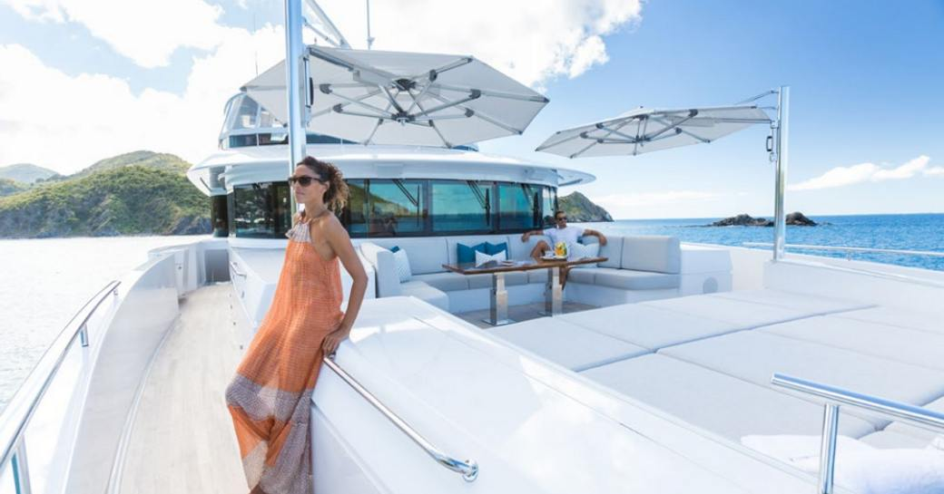 charter guest poses by the foredeck seating and sunning area on board motor yacht 'King Baby'