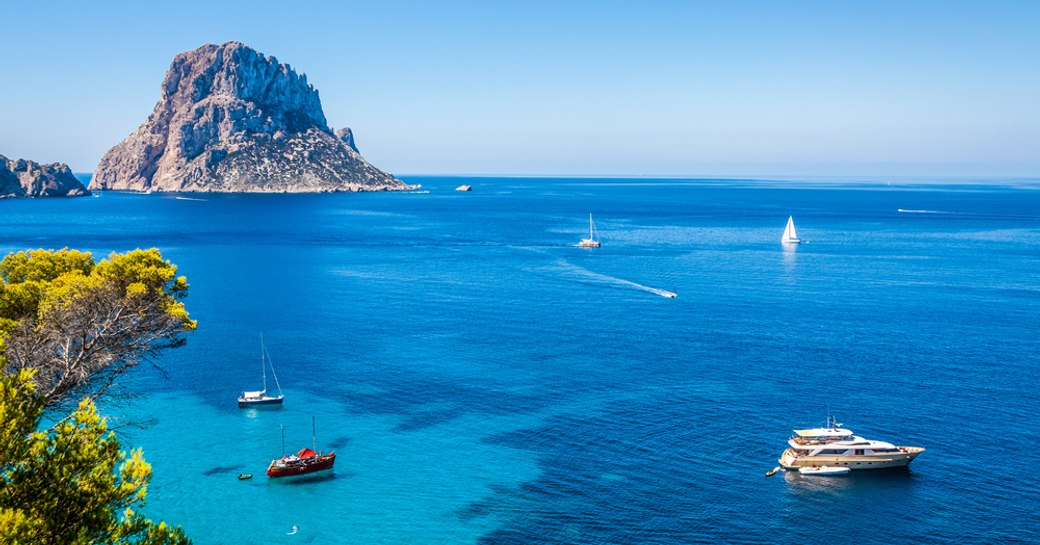 charter yachts bob along in the clear blue waters of ibiza, opposite the landmark of es vedra