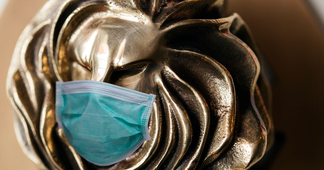 A Cannes Lions award wearing a facemask.
