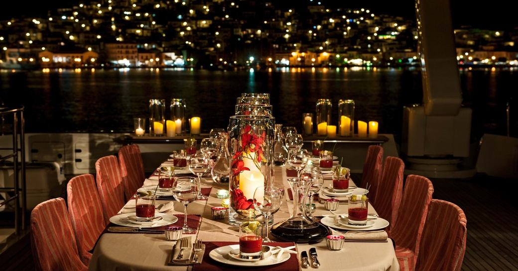 mediterranean coastlines lit up, with yacht and dining set up in foreground