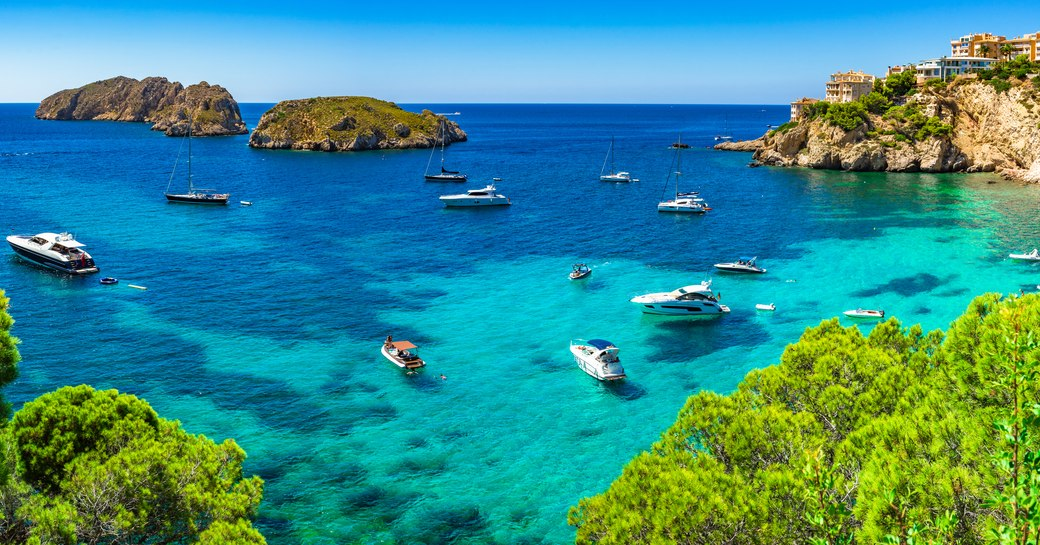 the beautiful and clear blue waters of a Mediterranean coast lined with superyacht