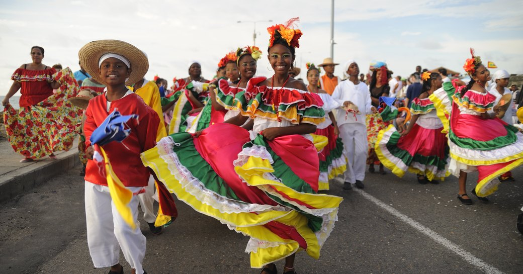happy dancers in bright and colourful traditional dresses  parade down a road in a carnival on the us virgin islands