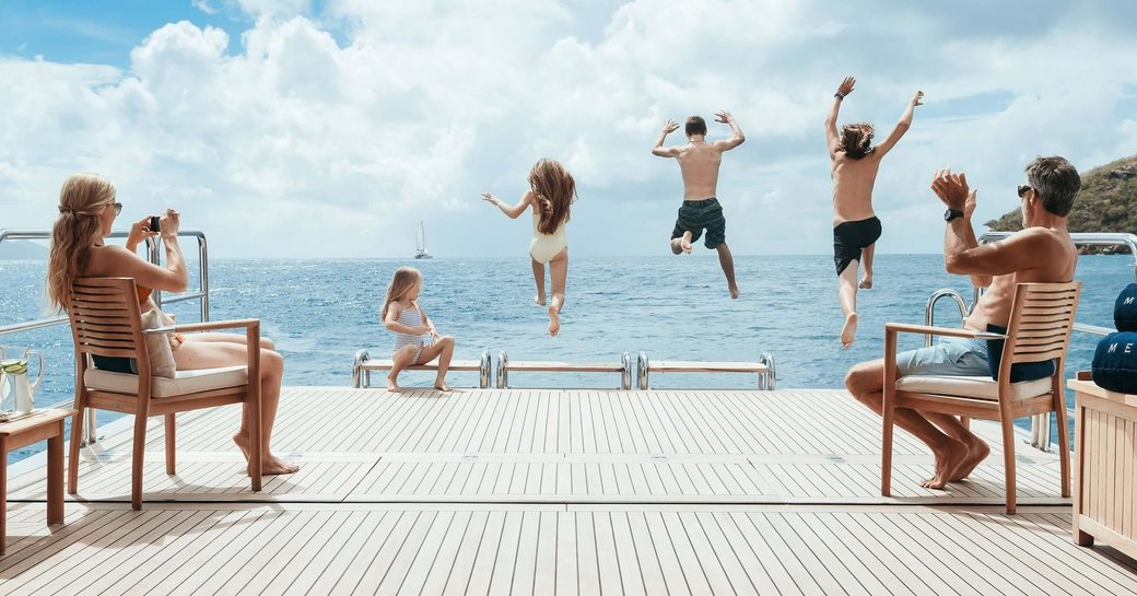 family jump off aft deck of superyacht