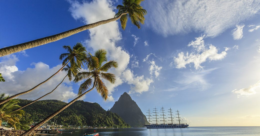 pitons of st lucia with palm trees and sandy beach in foreground