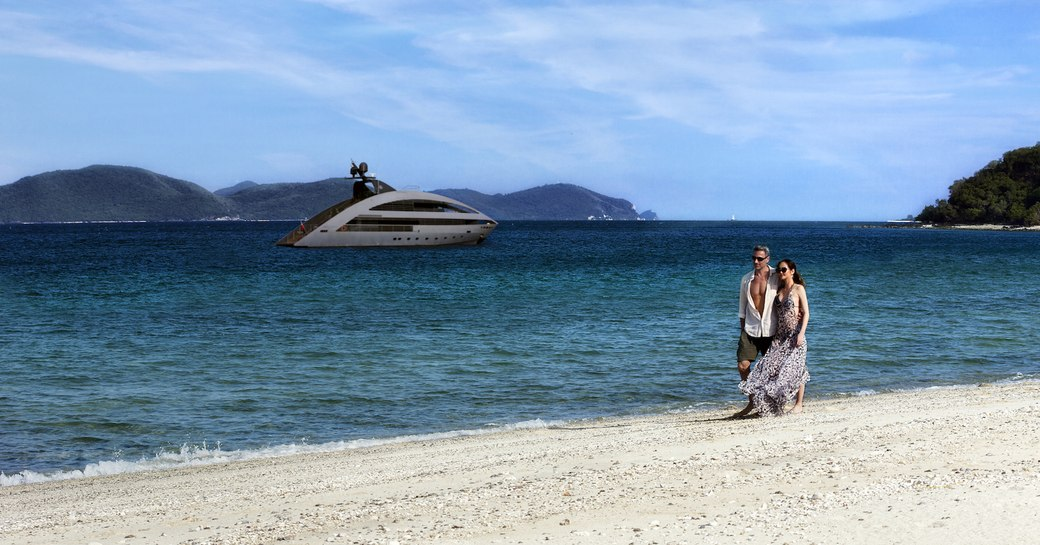 Couple on beach with motor yacht Ocean Emerald in distance.