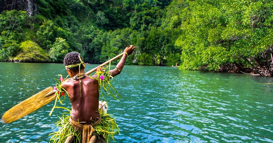boy rows boat in papua new guinea