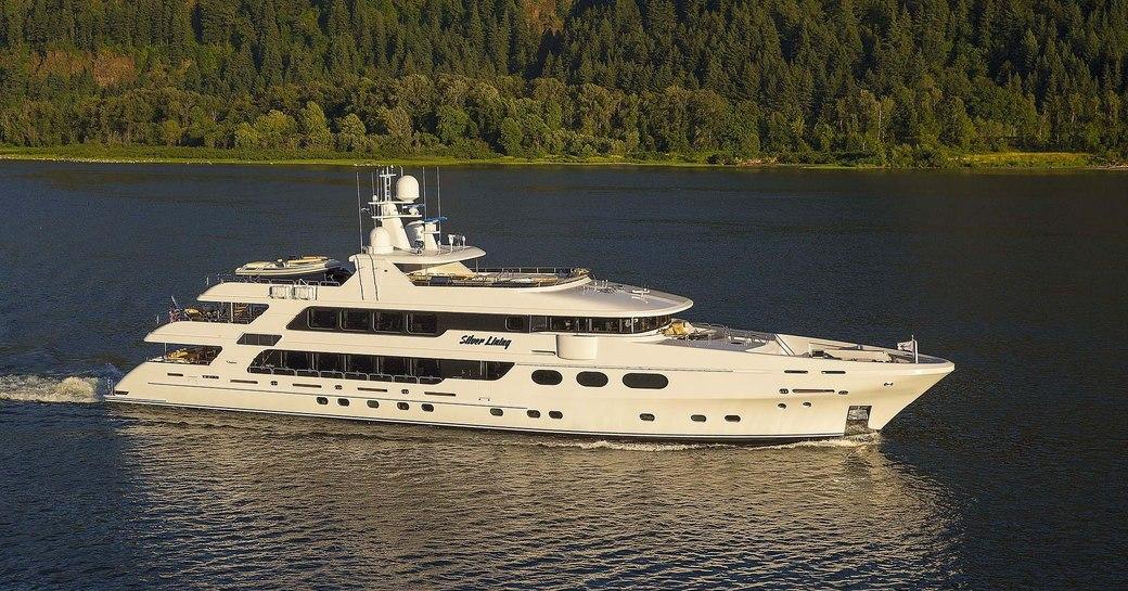 Superyacht Silver Lining cruising against a green coast