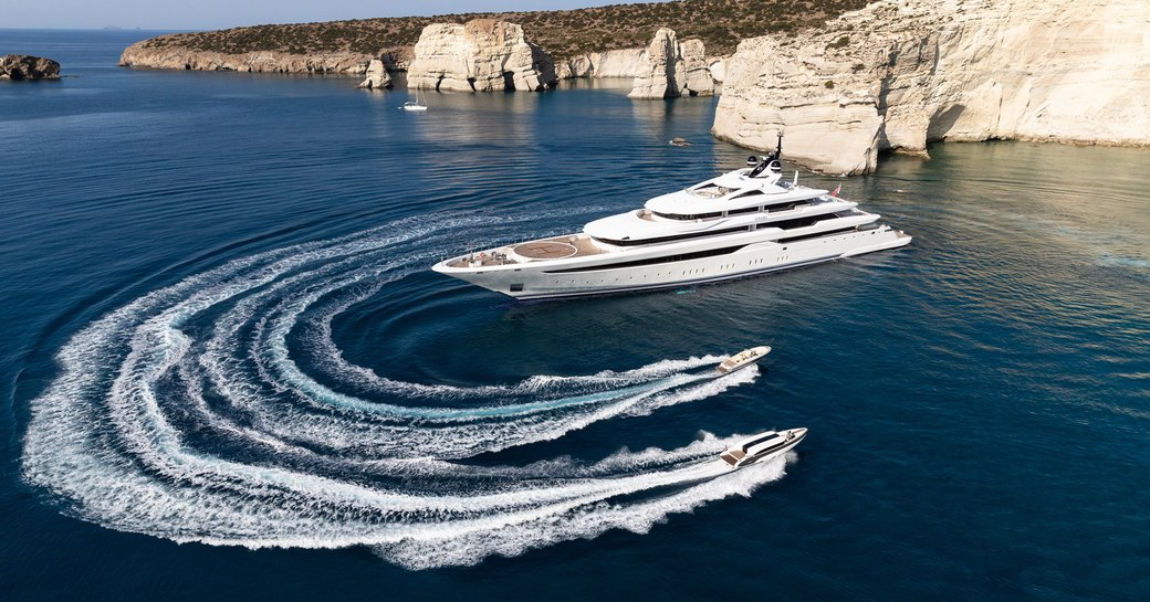 Superyacht O'PARI on water with dramatic coastline in background and two tenders nearby