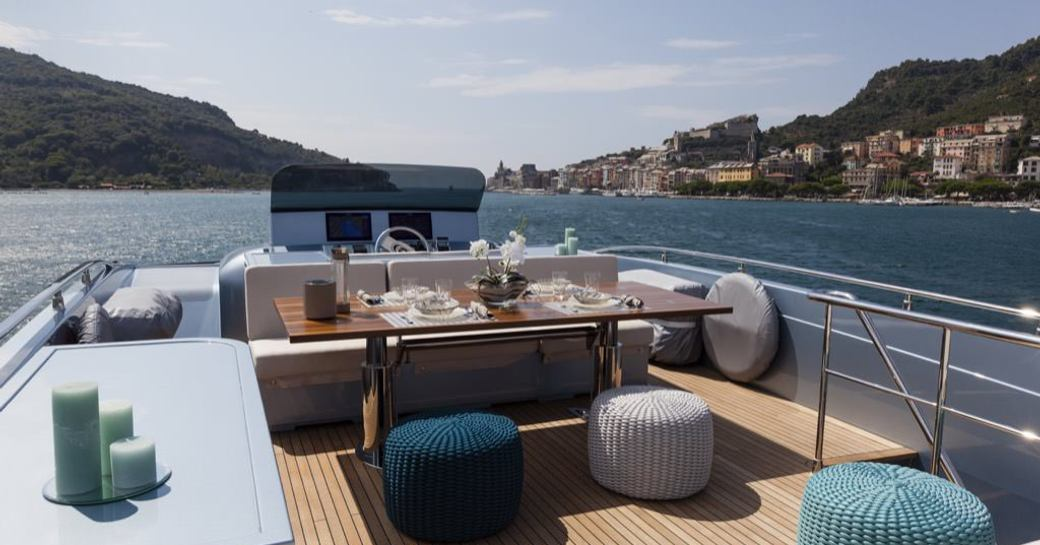 Table and comfortable seating on deck of superyacht 55 FIFTYFIVE