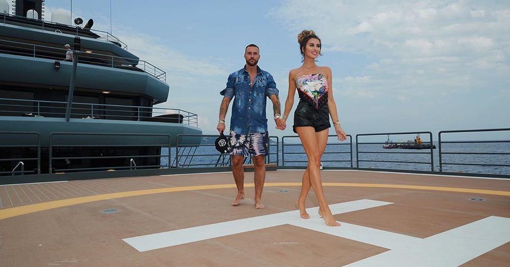 Designer Philipp Plein walking across helipad of explorer yacht RAGNAR with model
