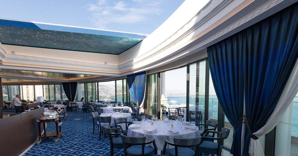 Dining room of Le Grill restaurant in Monaco, with glass ceilings, panoramic views and blue accents around the space