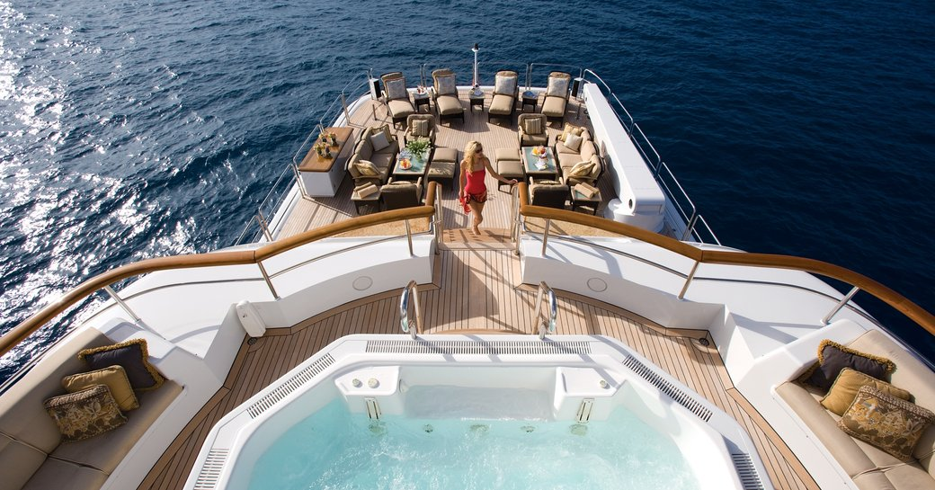charter guest ascends stairs to the Jacuzzi on the top deck of luxury yacht UTOPIA