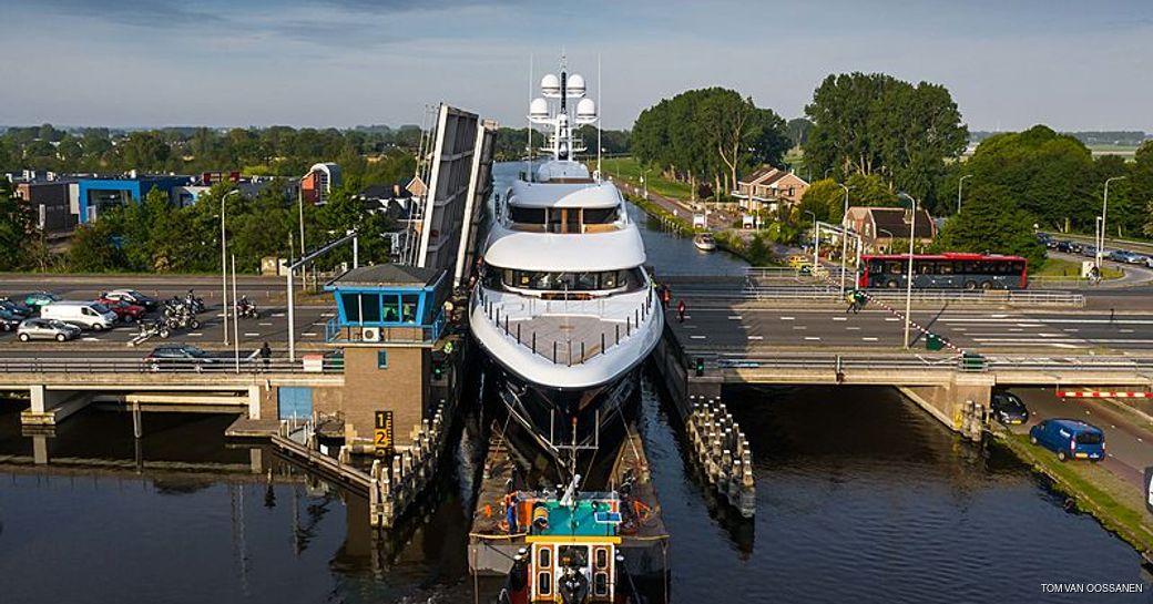 luxury yacht podium goes through gap in waterway canal