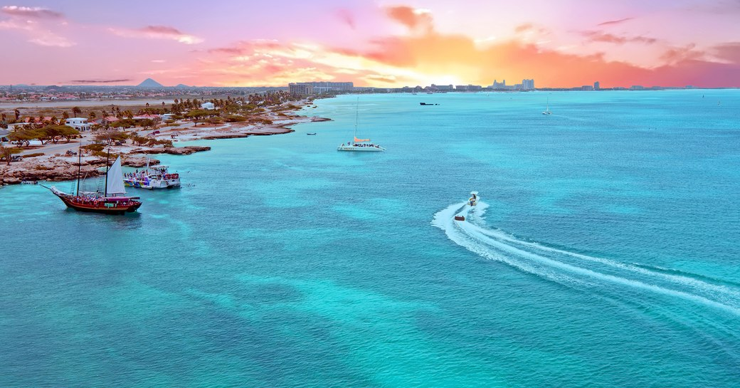 Aerial view from Aruba island in the Caribbean Sea at sunset with yachts on the water