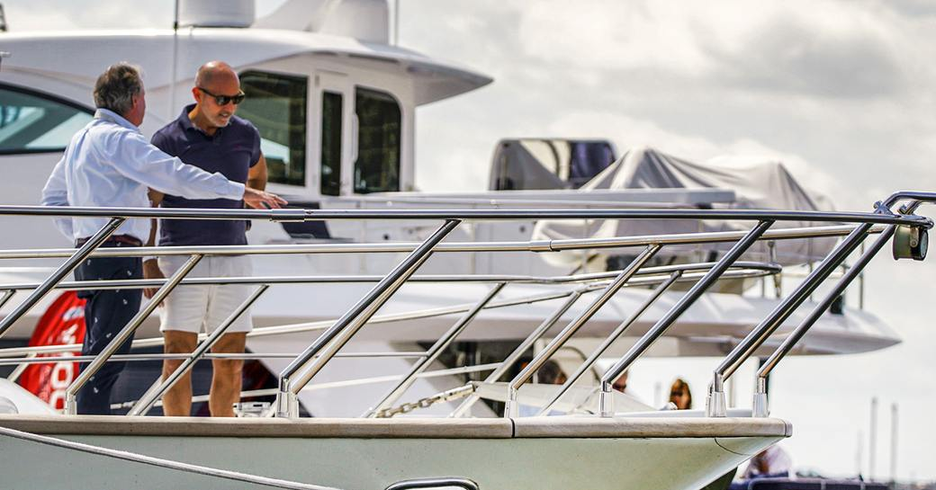 Two men in discussion on bow of motor yacht at Palm Beach International Boat Show.