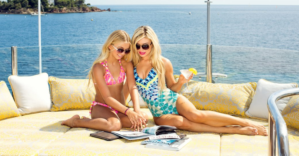 guests on board superyacht MY SEANNA read magazines together on an oversized sunpad on the sundeck
