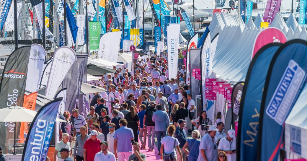 Visitors to Cannes Yachting Festival walking on red carpet looking at sailing boat displays on either side.