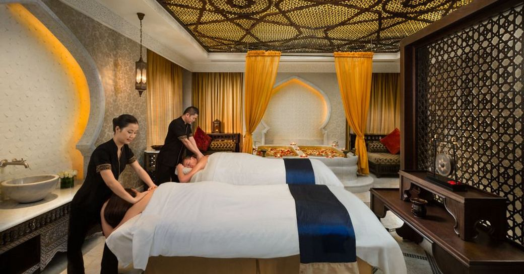 spa therapists give massages to two guests in an ornate therapy room
