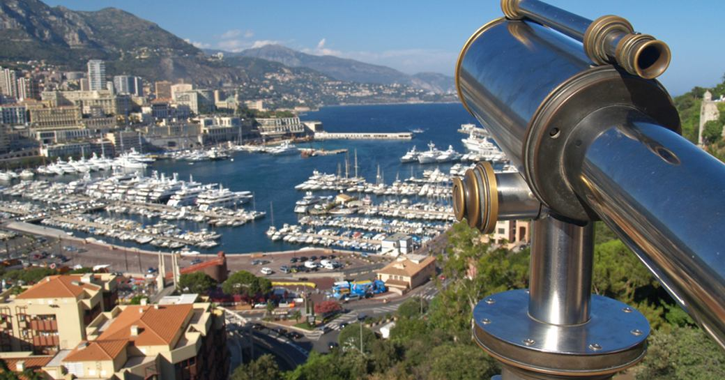 Elevated view of Monaco marina, telescope in foreground overlooks Monaco from hill top, with buildings cascading down to the marina.