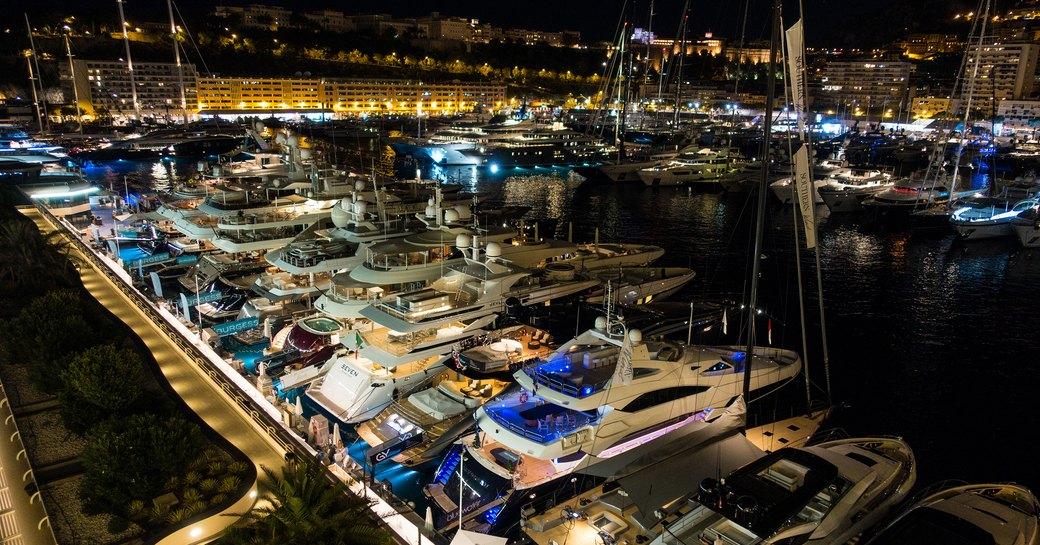 Yachts lined up at berth at night at Monaco Yacht Show 2018