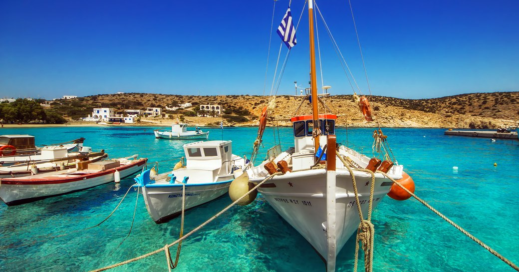 idyllic little harbour in greece, with boats bobbing on the water