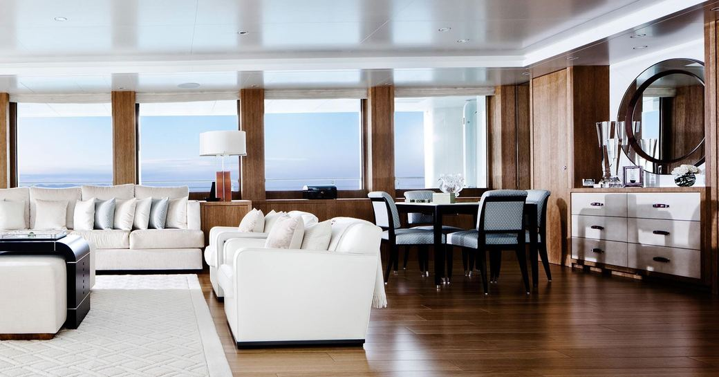 cool and contemporary main salon with white sofas and polished wooden floorboards on board superyacht Lady E