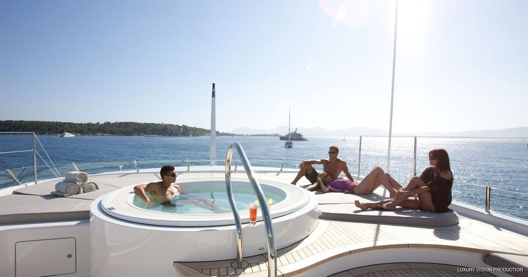 charter guests relax on sunpads next to jacuzzi on superyacht spirit