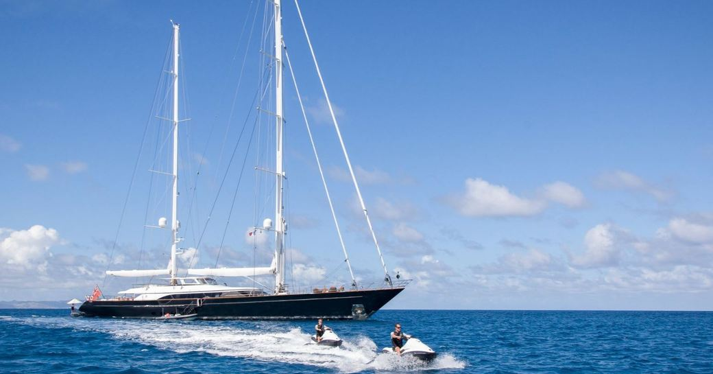 perini navi sailing yacht panthalassa at anchor with two charter guests using jet-skis around them