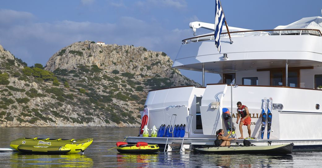 charter guests and crew on the swim platform with water toys on board luxury yacht ANCALLIA