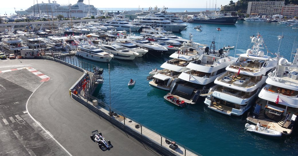 car drives past superyachts lined up in Port Hercules as part of the Monaco Grand Prix