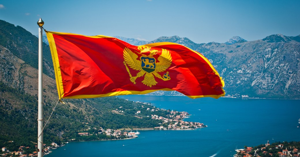 A Montenegrin flag waves in the wind above spectacular coastal landscape