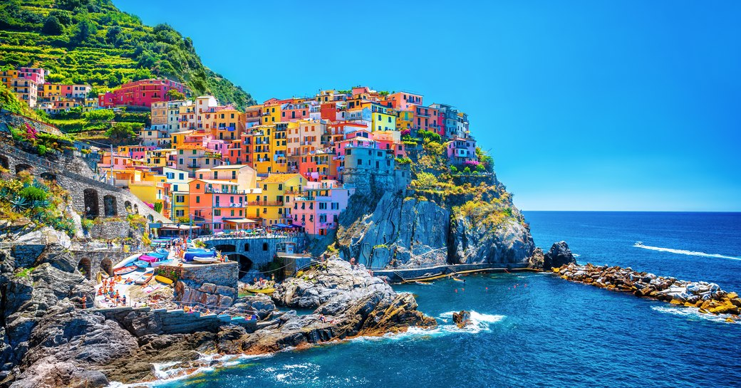 a coastal town in southern italy with houses painted in pastel hues overlooking the mediterannean sea