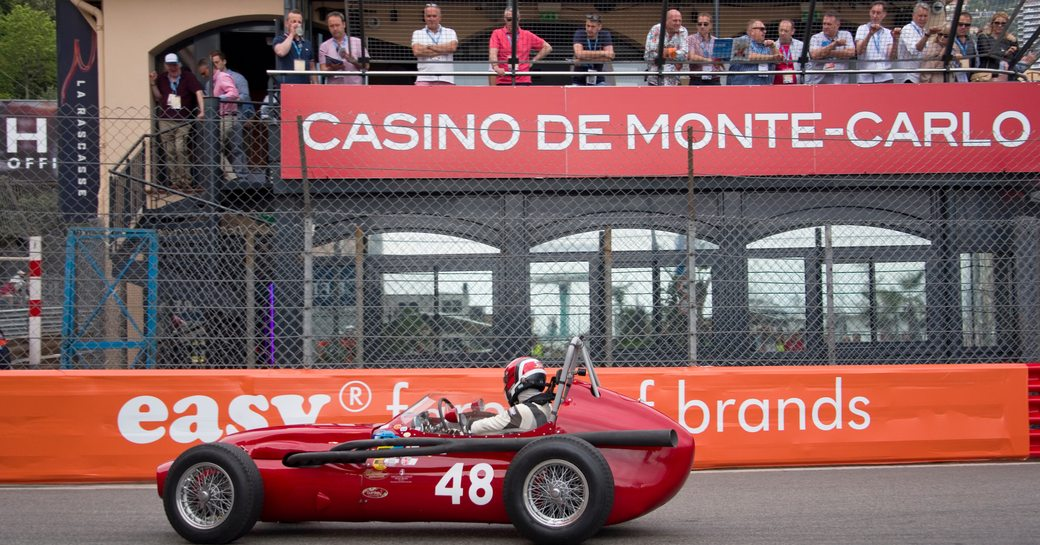 Racer in vintage red car at Monaco Historic Grand Prix, with Casino de Monte-Carlo sign in background with spectators watching from terrace.