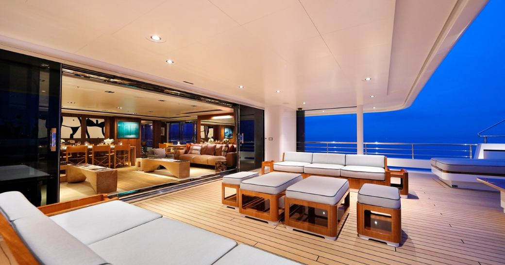 dining area al fresco on luxury yacht planet nine, with views of interior main salon in background