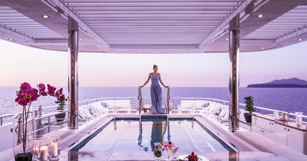 beautiful woman in dress ascending the pool stairs of superyacht Titania