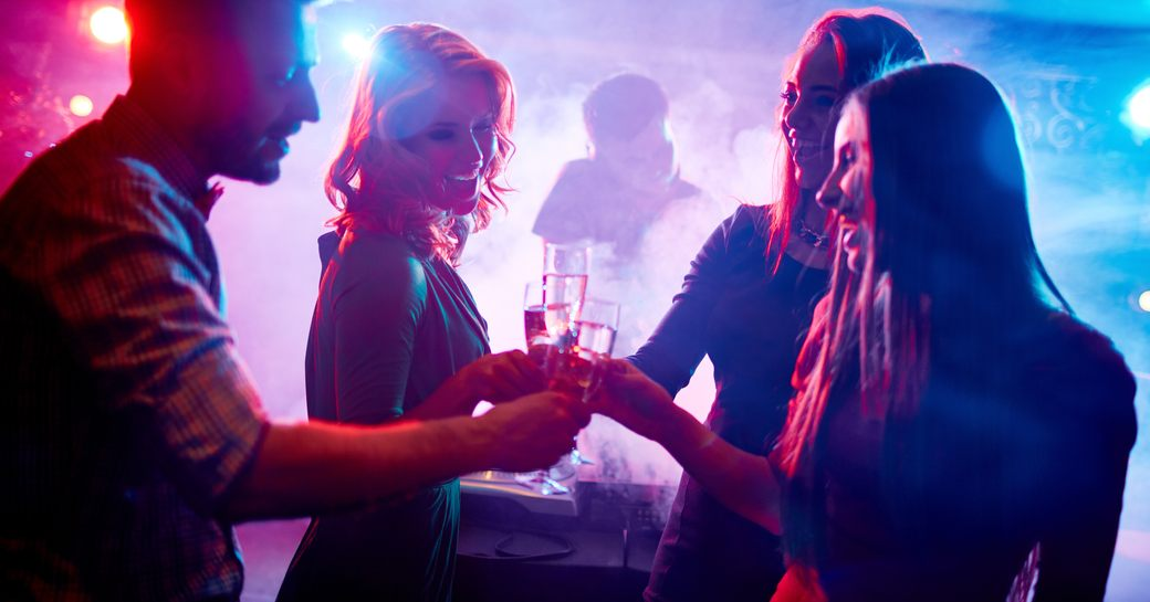 three female and one male clink champagne glasses at a nightclub
