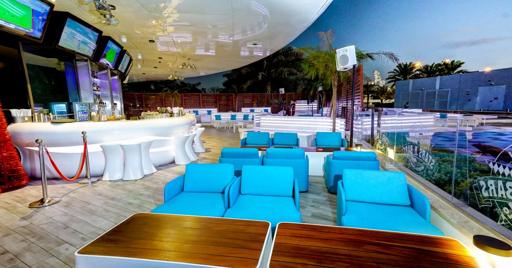 Outdoor terrace at Stars N Bars in Yas Marina, blue sofa seating and bar with television screens above