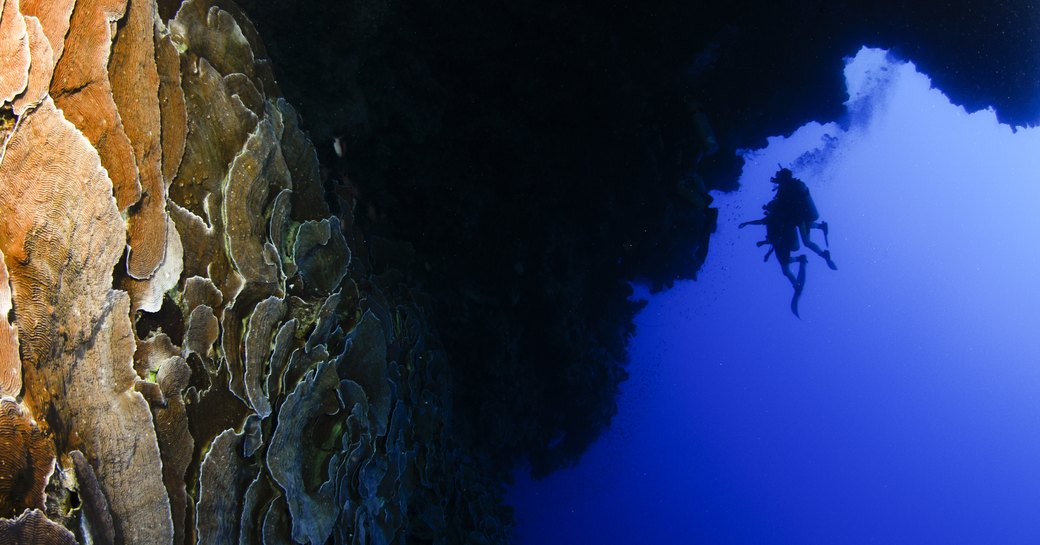 Scuba diver in distance of blue hole in Egypt