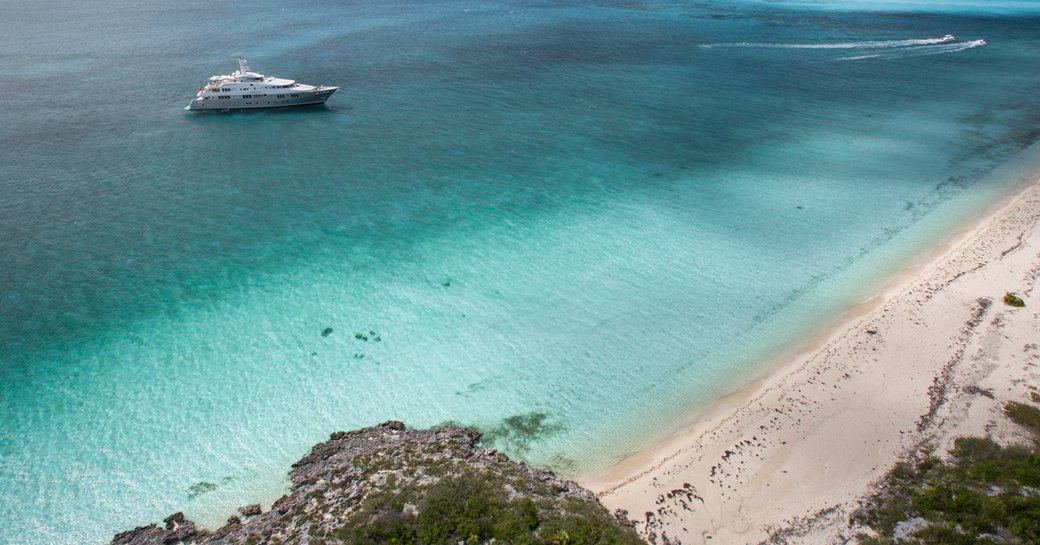 superyacht idles in the clear blue caribbean water opposite sandy beach