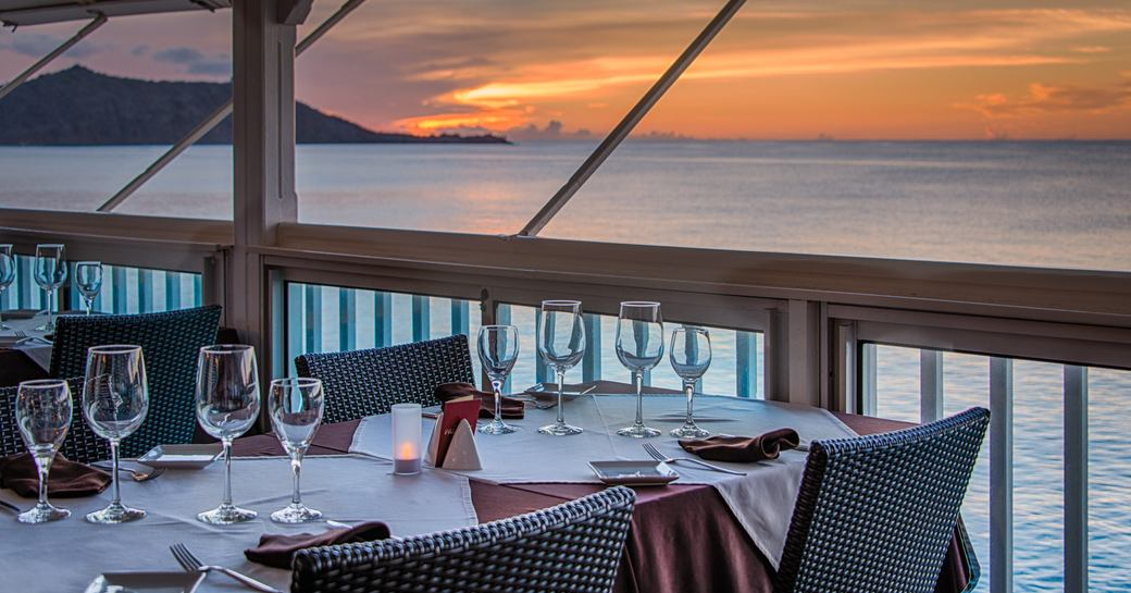 beach-side table is set for dining as the sun sets over the horizon in St Martin